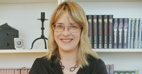 Woman with blonde hair and wearing glasses standing in front of a bookshelf with books and a candle stick holder on the shelves. The woman is smiling.