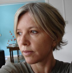 Image of Miro Bilborough. Woman's face, pixie short blonde hair. Her eyes are away from the camera looking to the bottom left of the image.