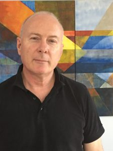 portrait of author Paul hetherington who is wearing a black shirt and looking unsmiling at the camera. The wall behind is angular graphic painting